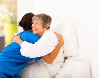 caregiver and elderly woman embracing